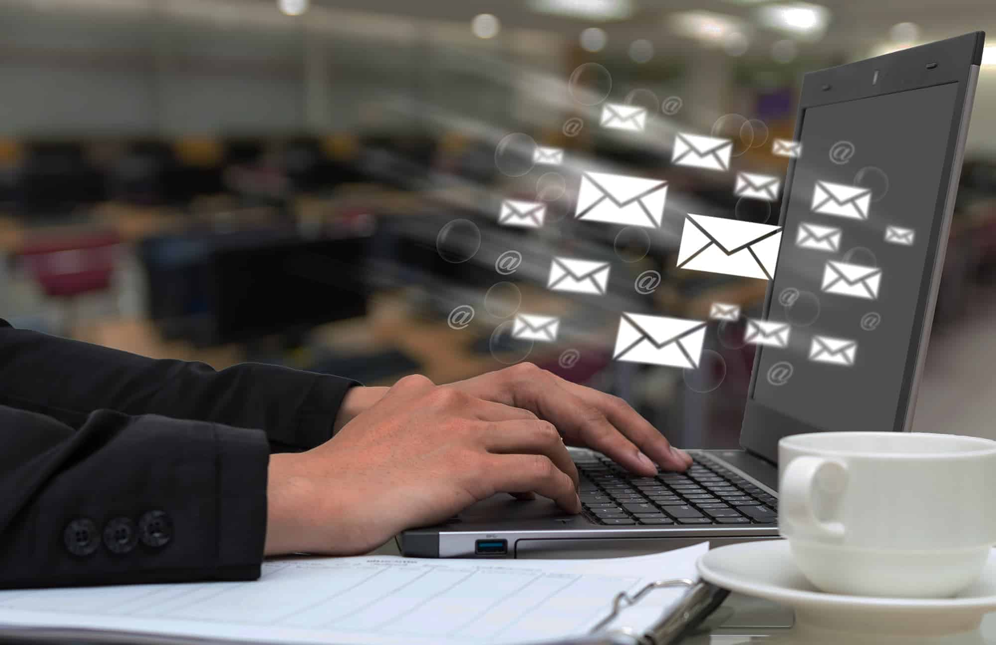 Marketing to Families - man typing on computer with images of direct mail being sent digitally as an email.